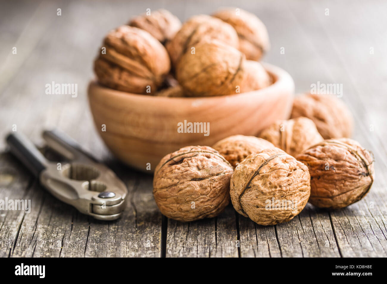 Tasty dried walnuts and nutcracker on old wooden table. - Stock Image