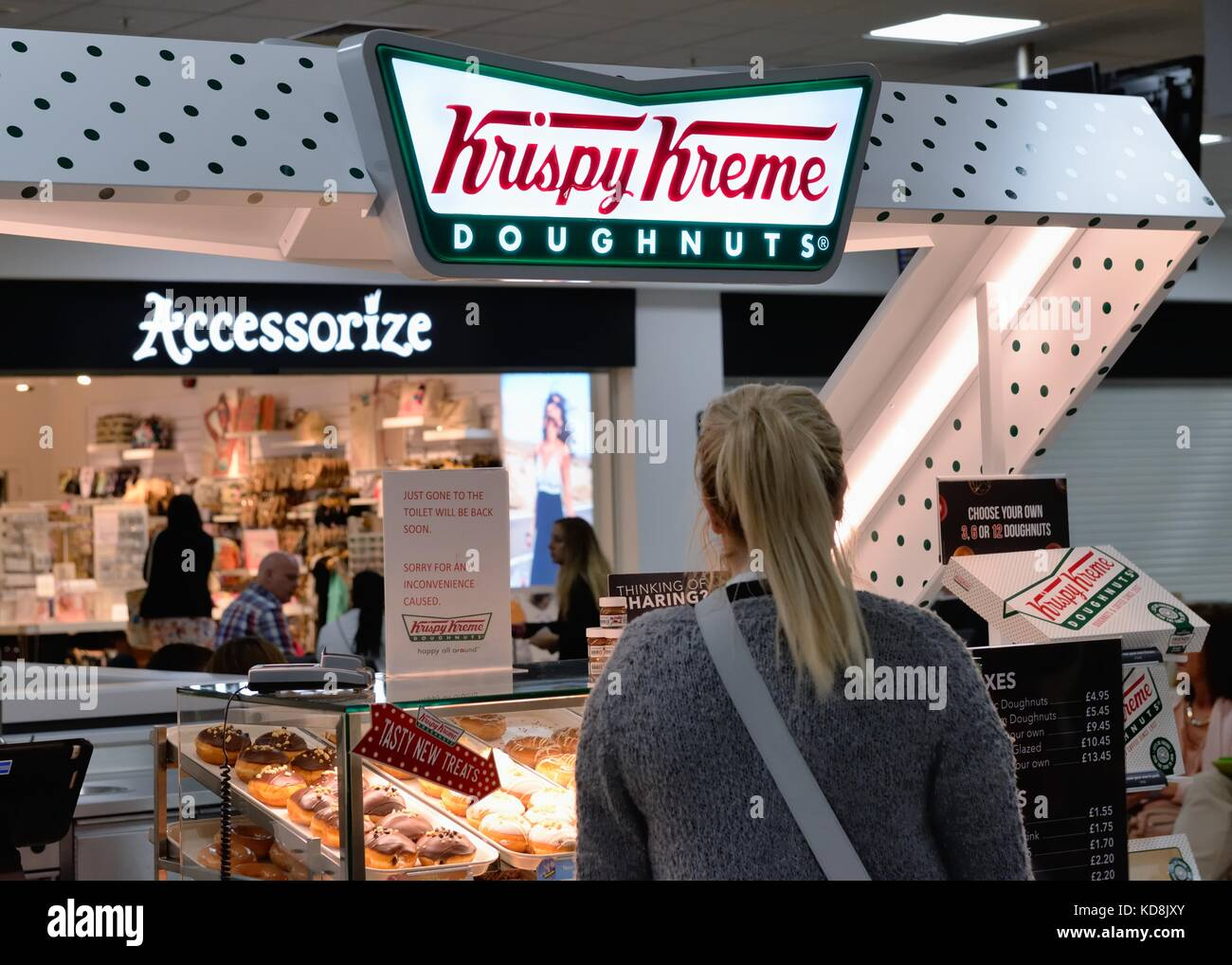 A woman standing by a Krispy Kreme doughnut stand at Glasgow international airport, Scotland, UK - Stock Image