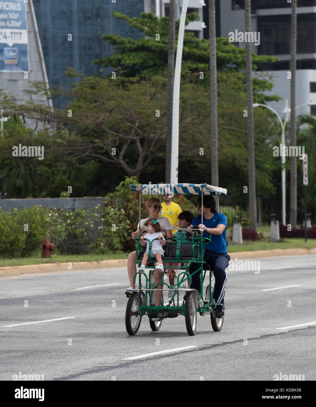 Family on a four wheel cycle traffic free area on Sunday in Panama City - Stock Image