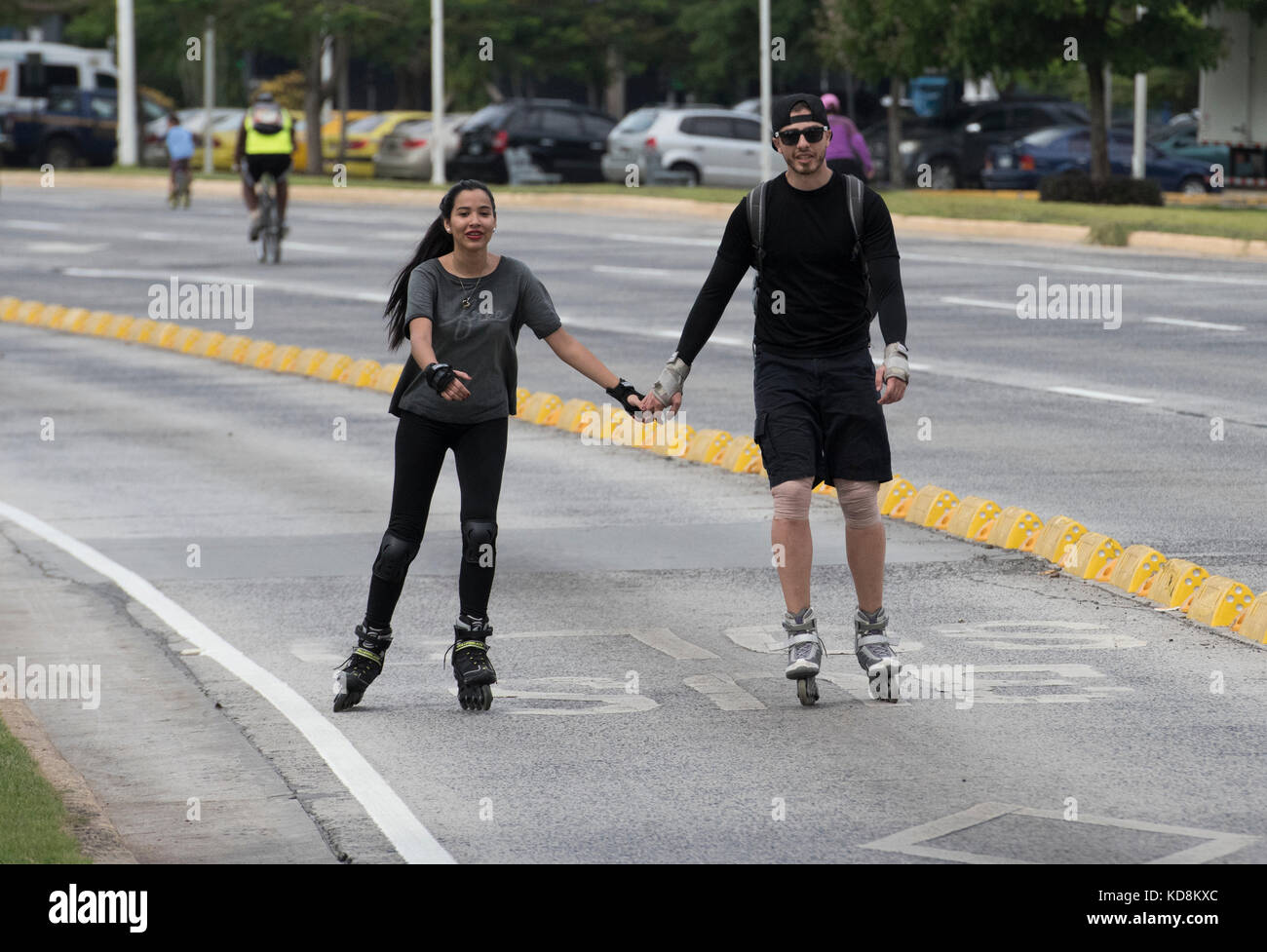 Couple roller blading in the traffic free area on Sunday in Panama City - Stock Image