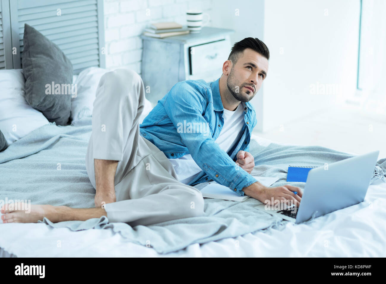 Pensive freelancer lying in bed while working from home - Stock Image