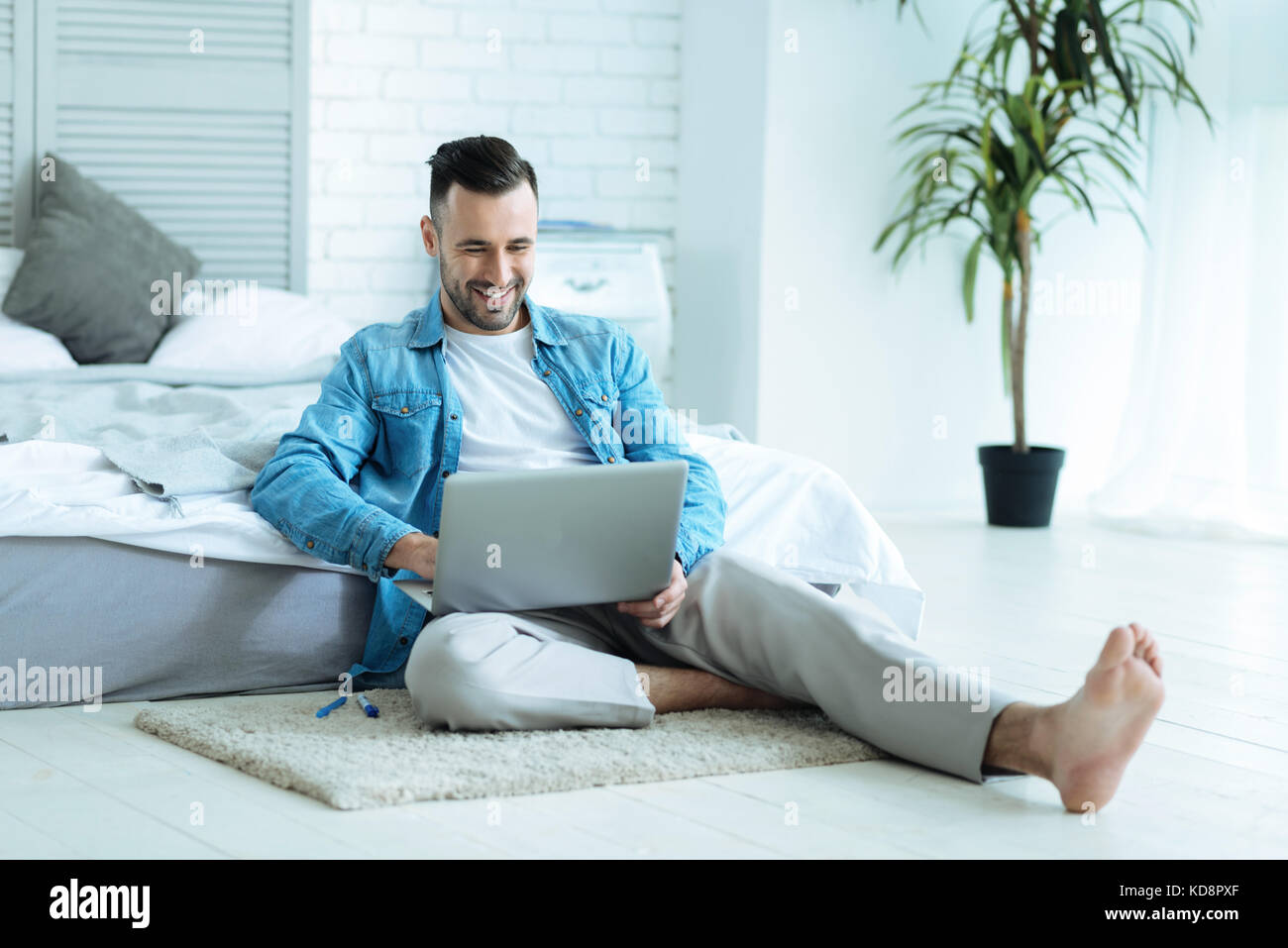 Happy self employed man smiling while working from home - Stock Image