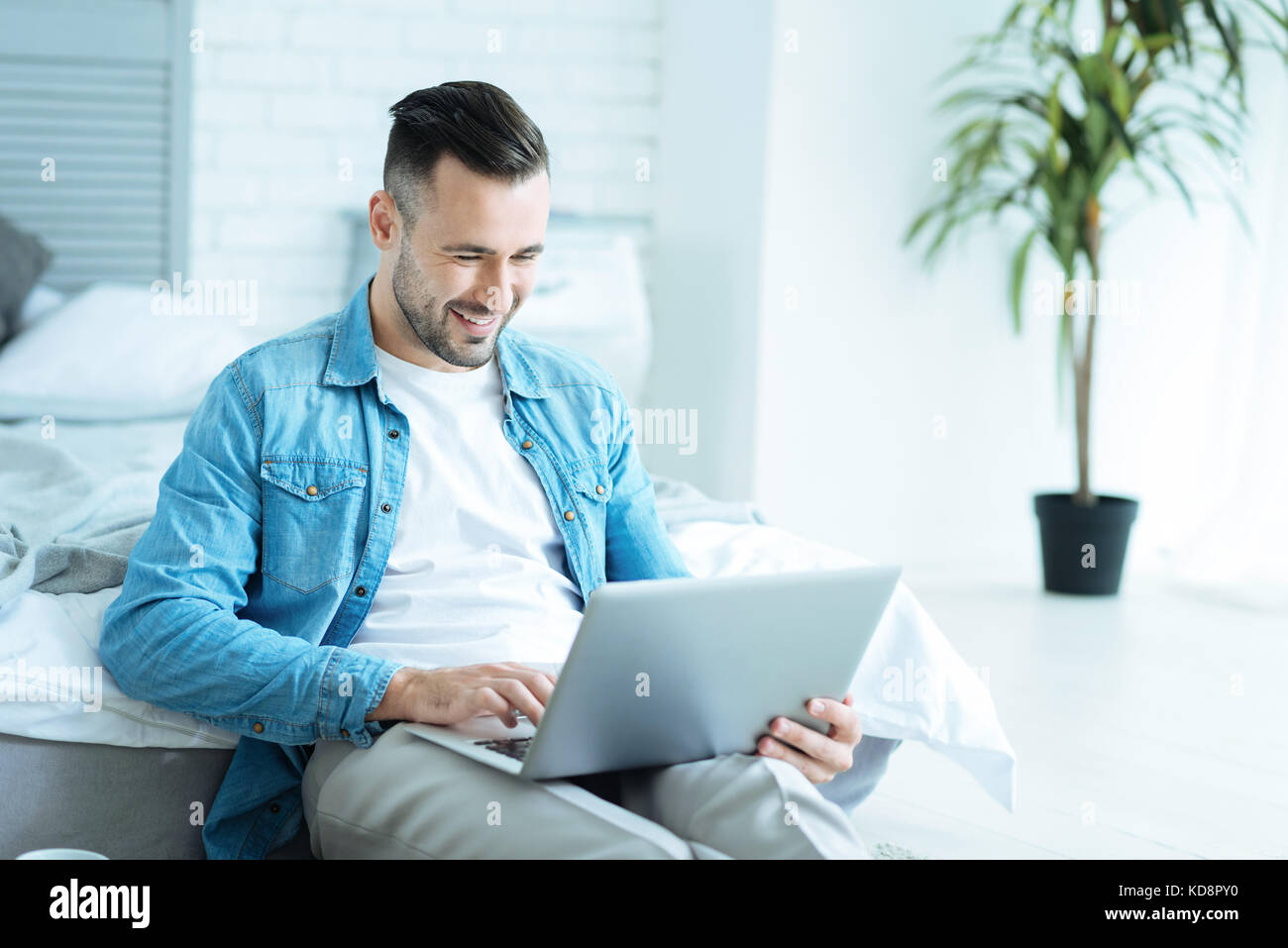 Joyful man grinning broadly while using laptop - Stock Image