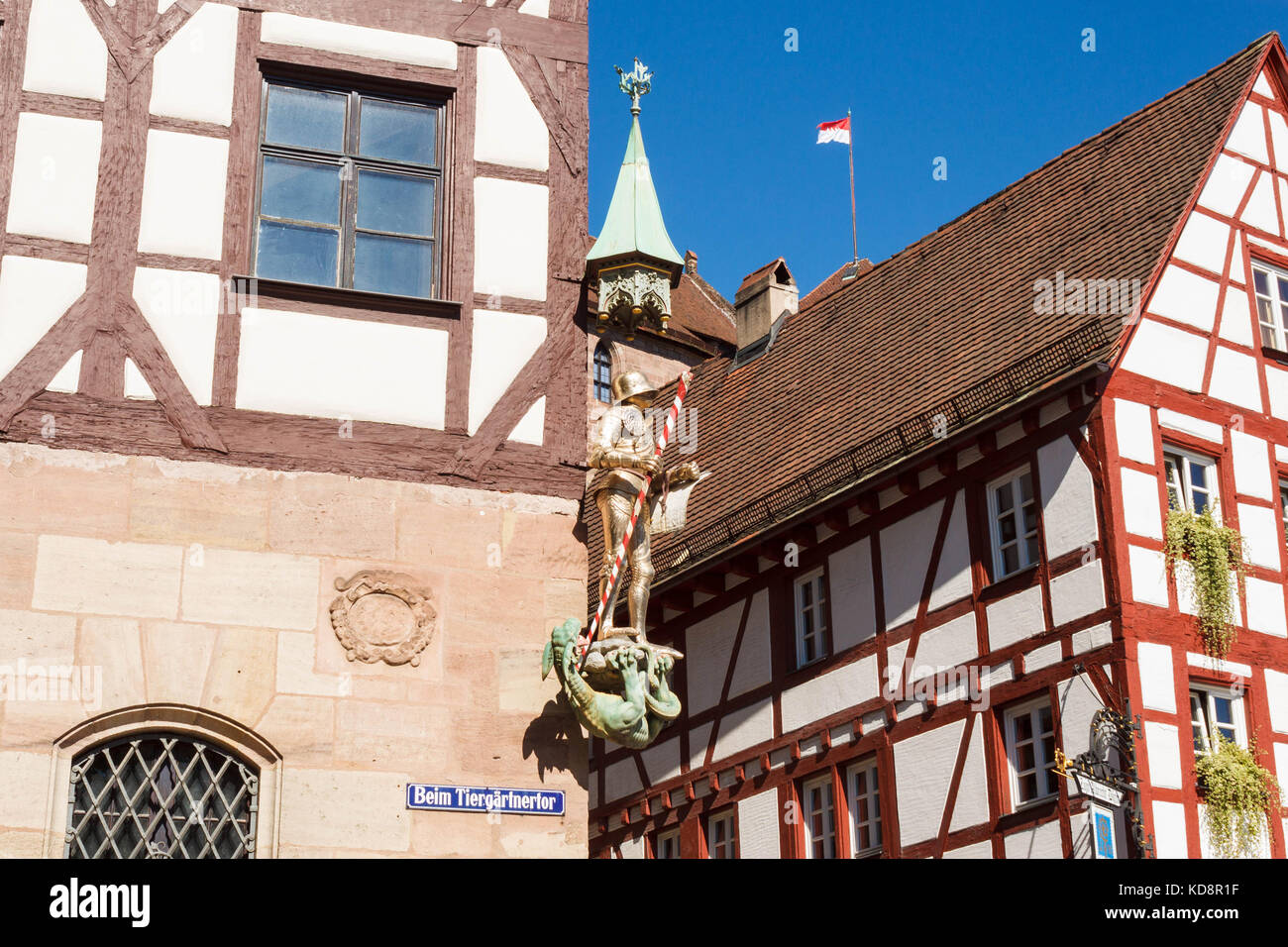 Pilatushaus (Pilatus house) in the old town of  Nuremberg. A statue of St. George in golden armour  defeating the - Stock Image