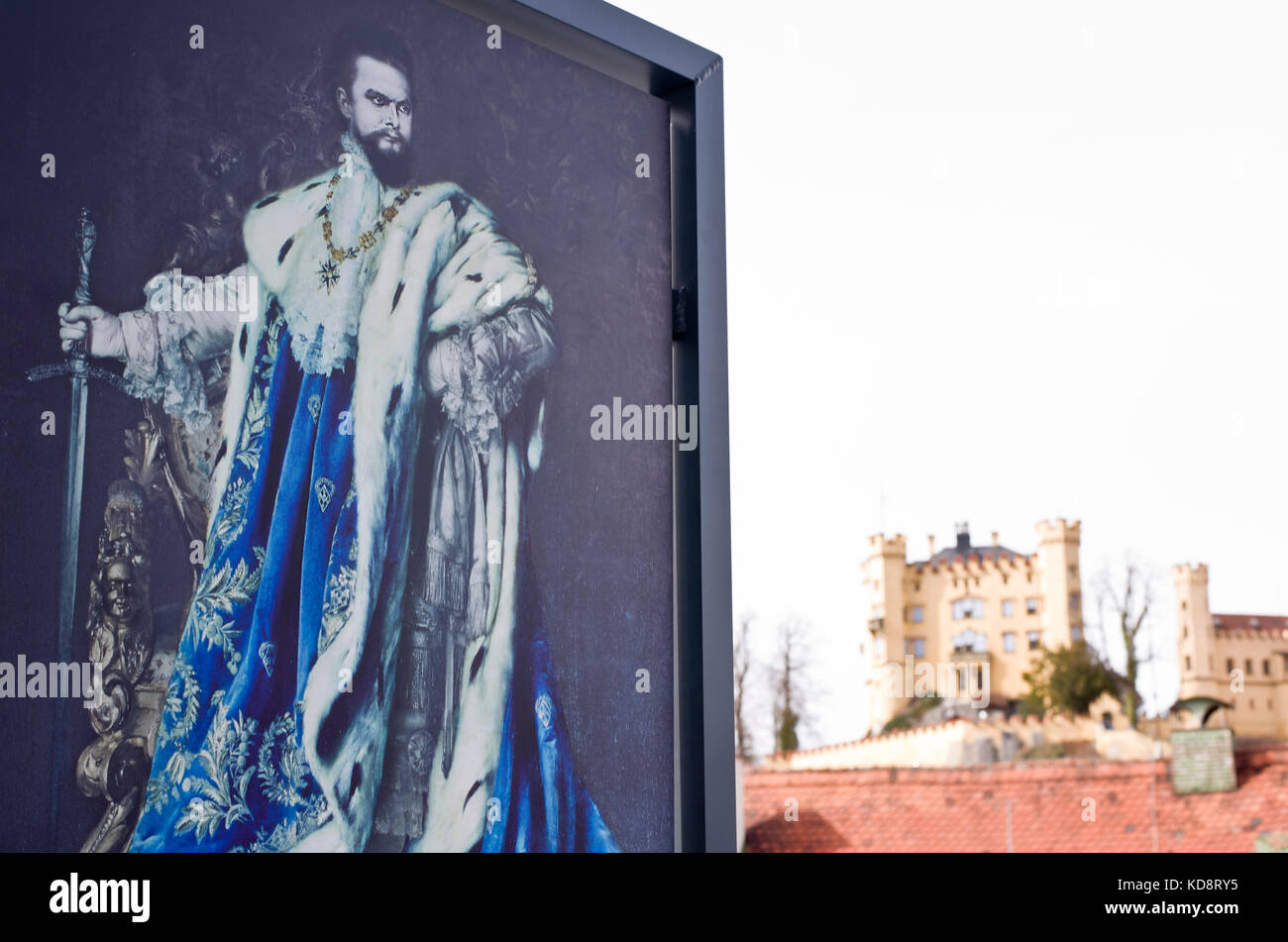Poster image of King Ludwig 2 of Bavaria, with the regal Romanesque Revival home of Hohenschwangau castle in background, - Stock Image