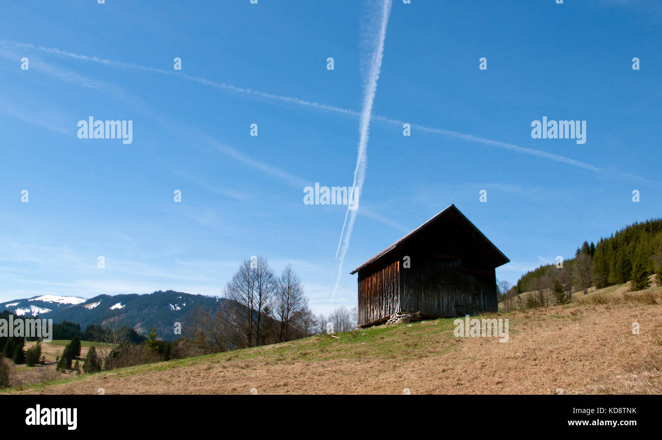 Aircraft contrail clouds high up in the blue skies over the mountain exclave quadripoint border village of Jungholz, - Stock Image