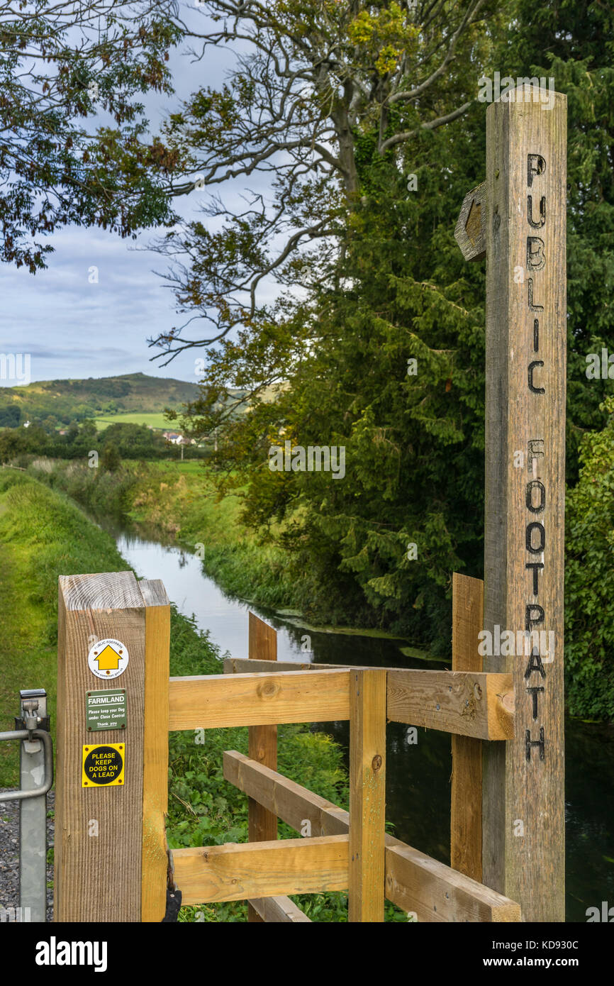 A Public Footpath sign shows the right of way along a small stream in Somerset, England. - Stock Image