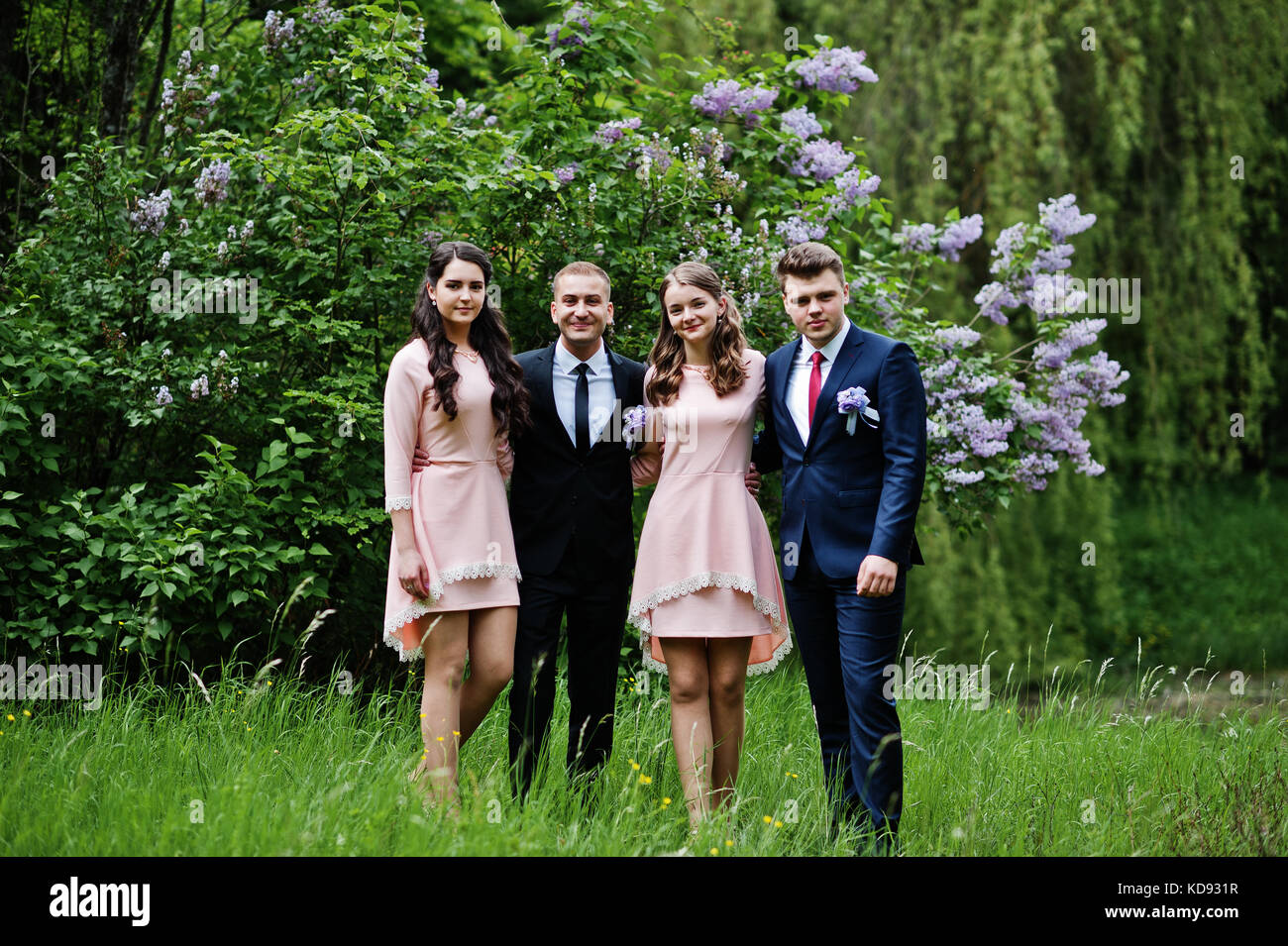 7e794c6bd90 Bridesmaids in pink dresses posing with handsome groomsmen in tuxedos in  the park with blossoming trees in the background.