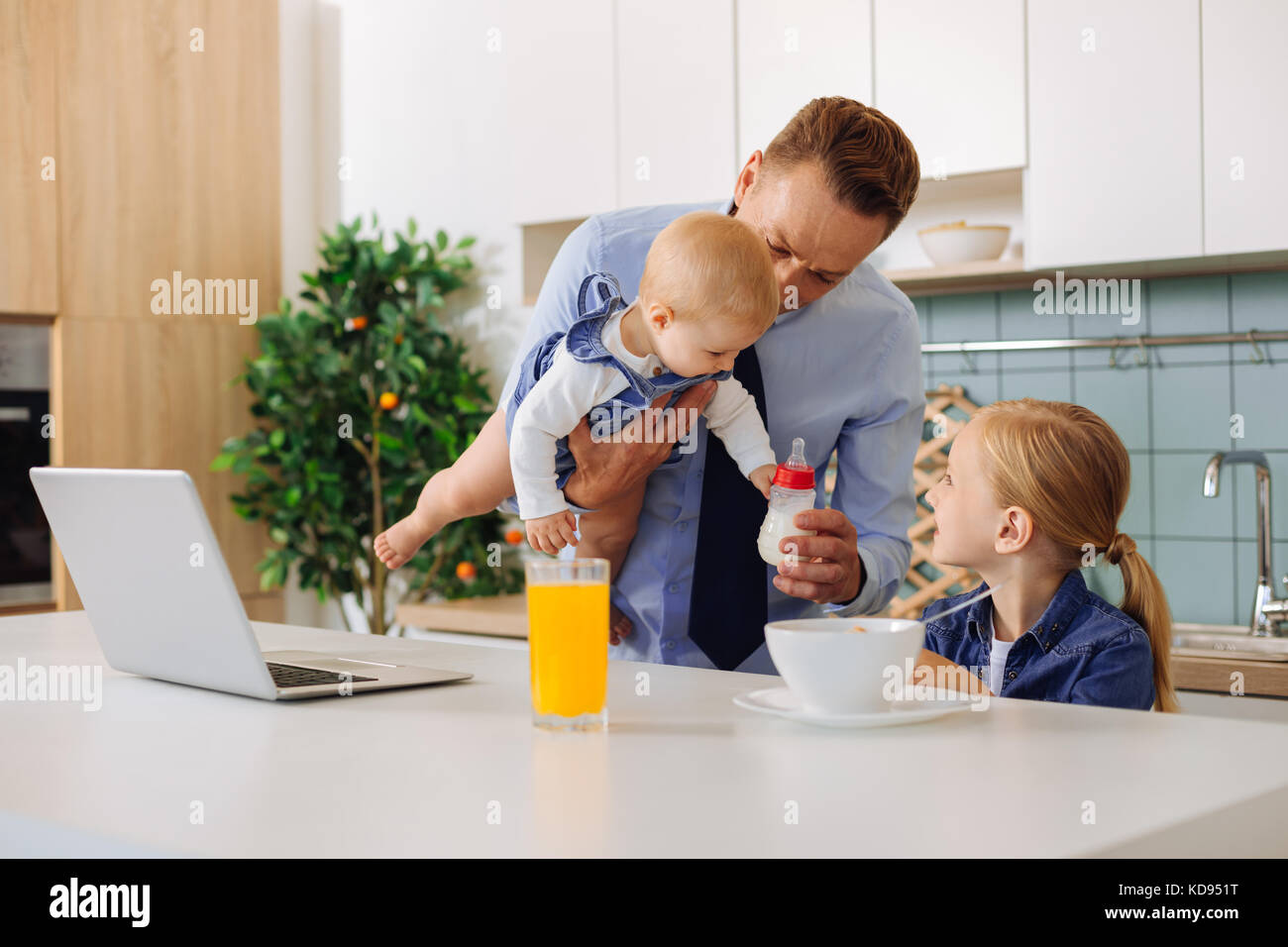 Pleasant handsome man holding a bottle with milk - Stock Image