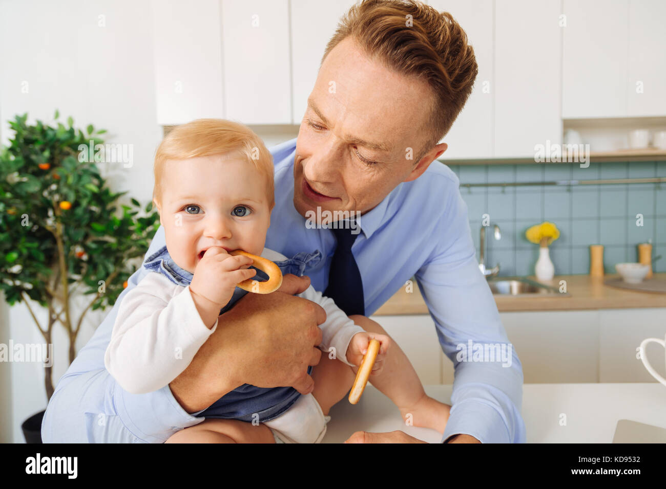 Cute baby child holding a bagel - Stock Image