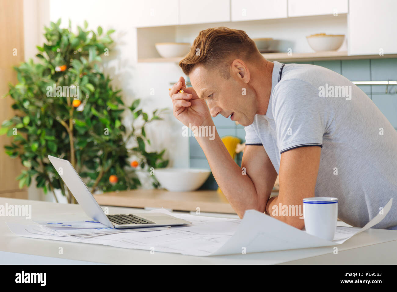 Unhappy sad man working at home - Stock Image