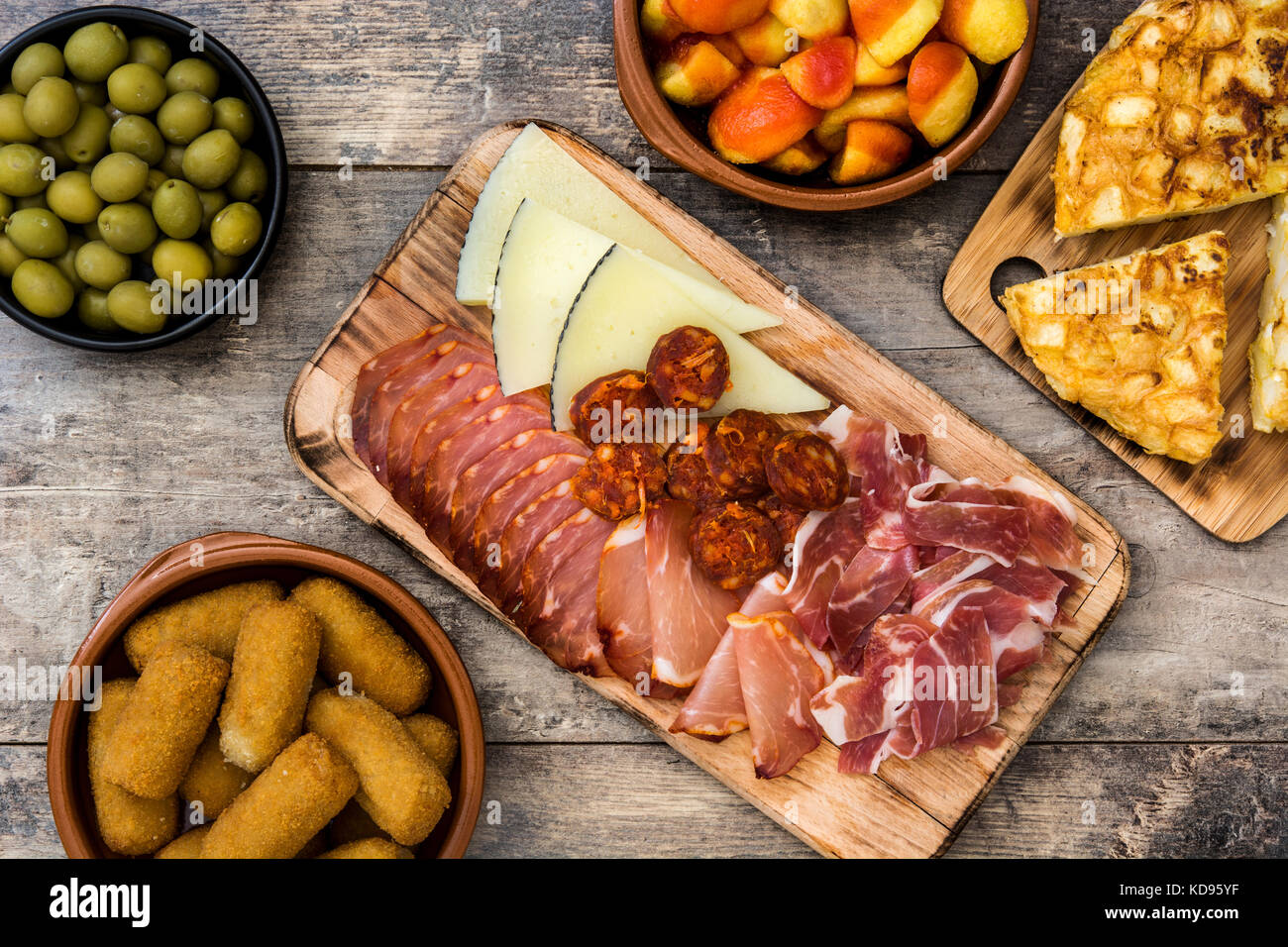 Traditional spanish tapas. Croquettes, olives, omelette, ham and patatas bravas on wooden table Stock Photo