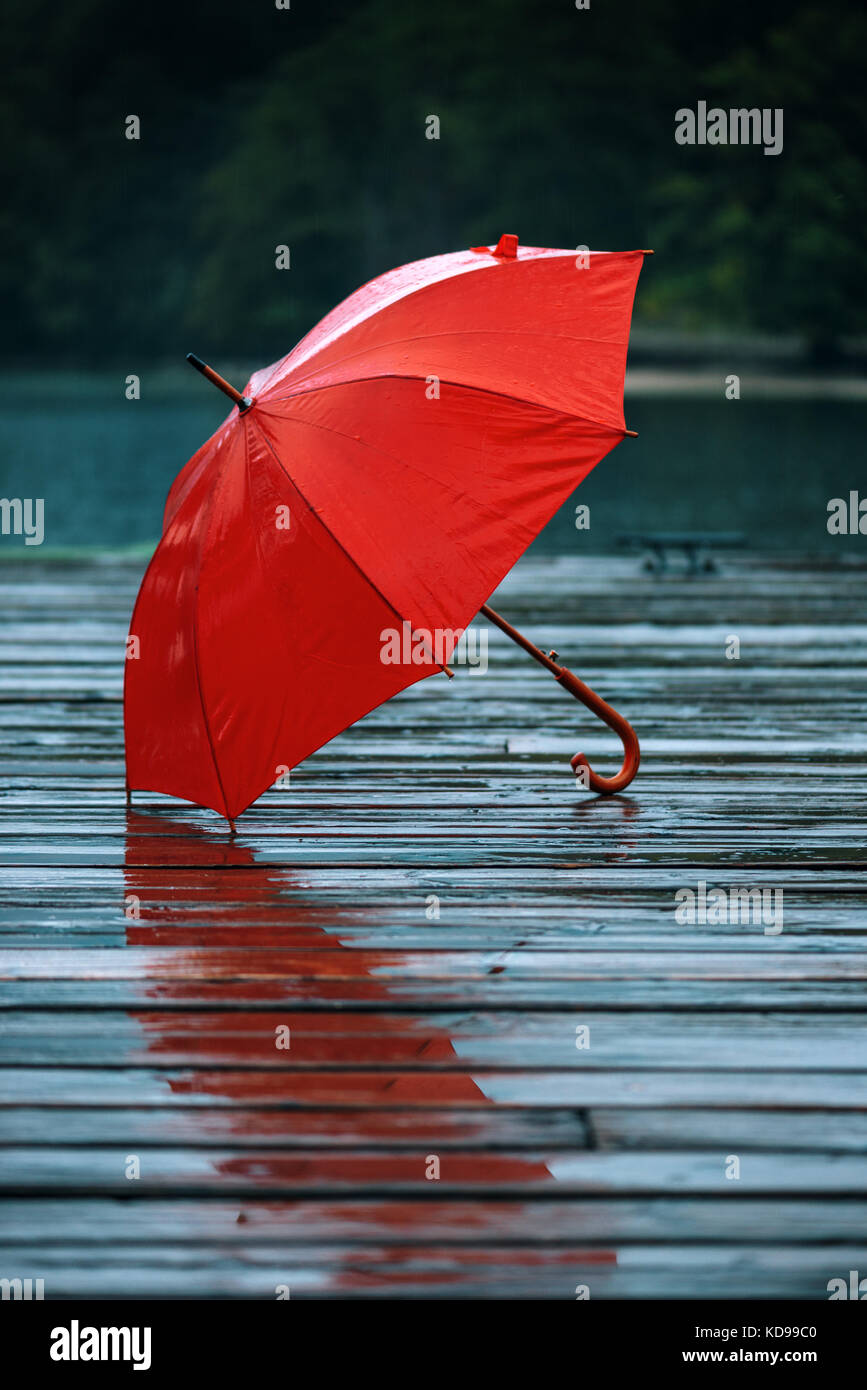 Red umbrella on dock. Forgotten personal accessory on wooden pier on autumn rain. - Stock Image