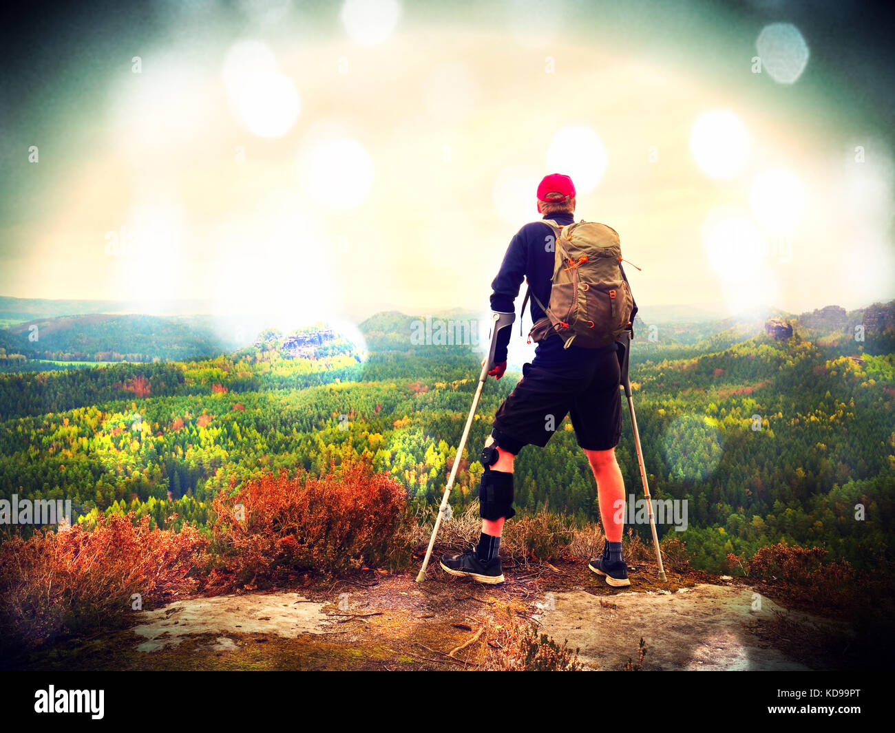 Lens defect. Man hiker Wearing Supportive Leg Brace and gainst the cruthes. Natural forest park in background - Stock Image