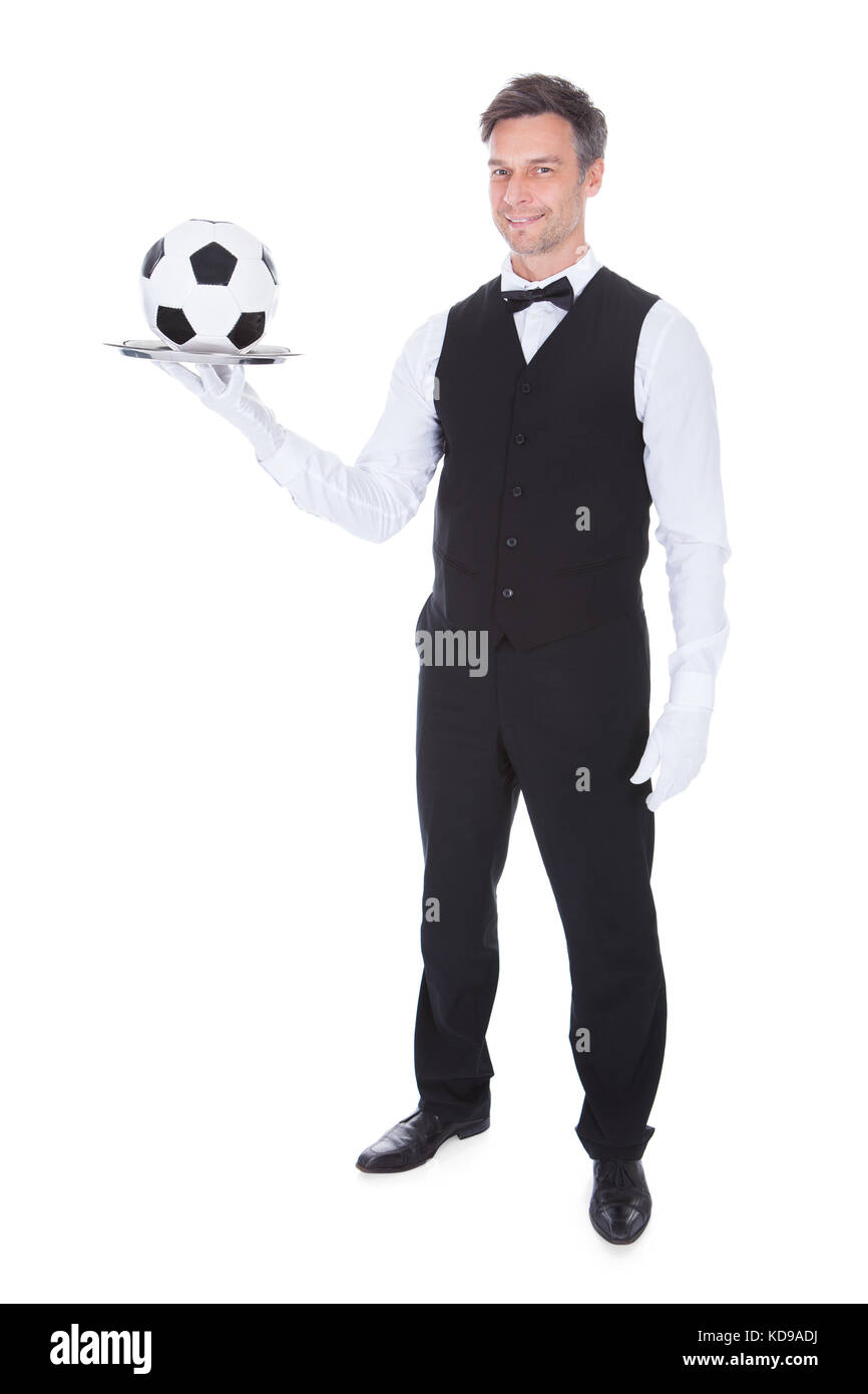 Portrait Of Happy Male Waiter Holding Football In Tray Stock Photo