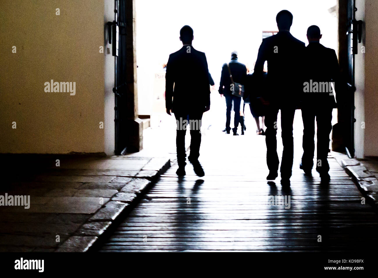 group of men in suits walking - Stock Image