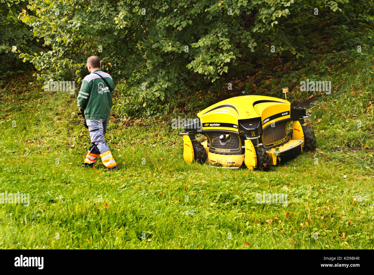public park maintenance may with robotic lawnmower - Stock Image