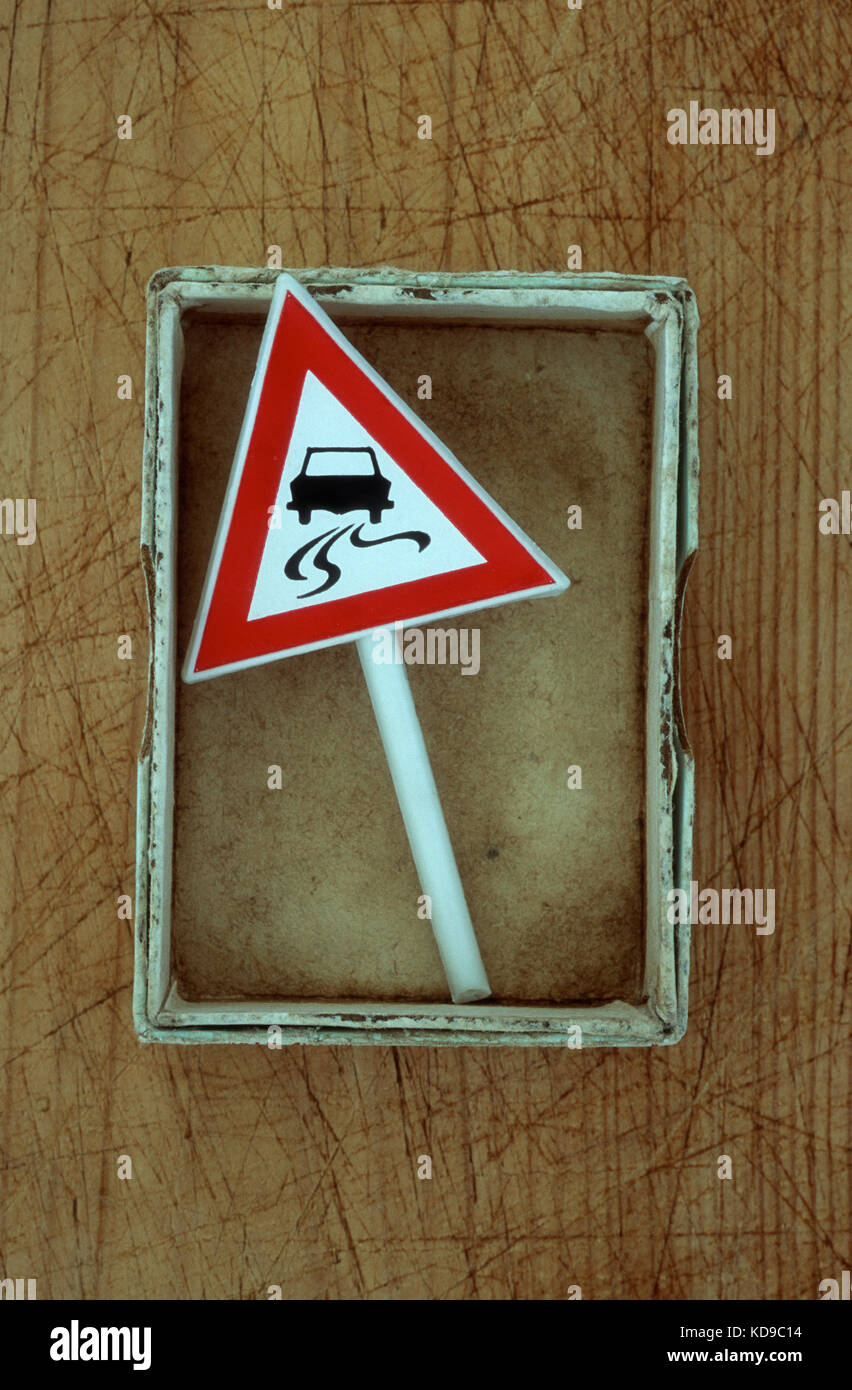 Small box containing model of roadsign with image of car skidding on slippery road - Stock Image