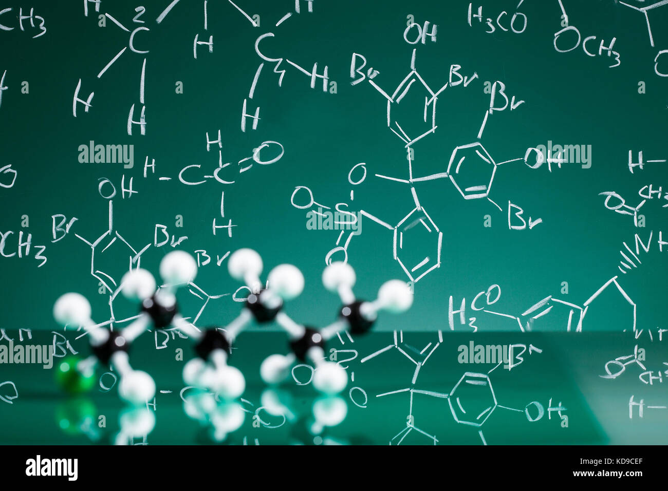 Model of molecular structure on green reflective background - Stock Image