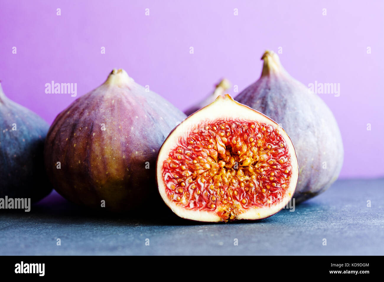 Colorfull still life organic ripe figs on stony table, beautiful purple violet background. Selective focus on sliced - Stock Image