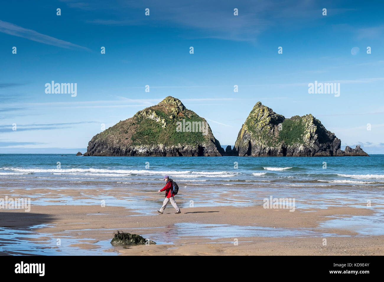 Holywell Bay Cornwall - a walker on the beach at low tide at Holywell Bay with the iconic Gull Rocks in the background - Stock Image