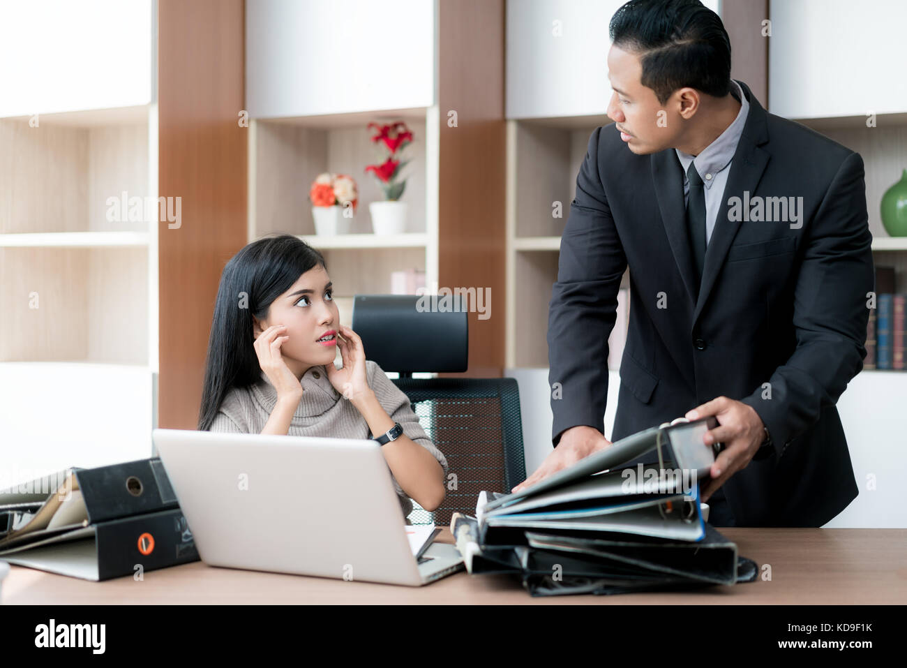Anger businessman manager taking folders on his subordinate table. Businesswoman under stress due to excessive work. - Stock Image