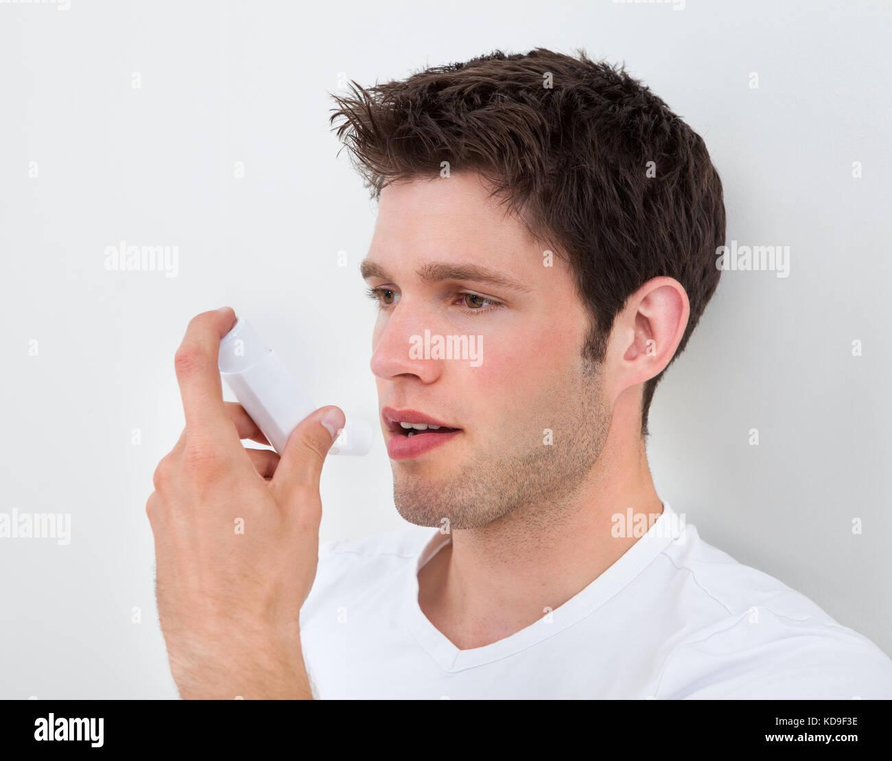 Young Man Holding An Asthma Medicine Inhaler - Stock Image