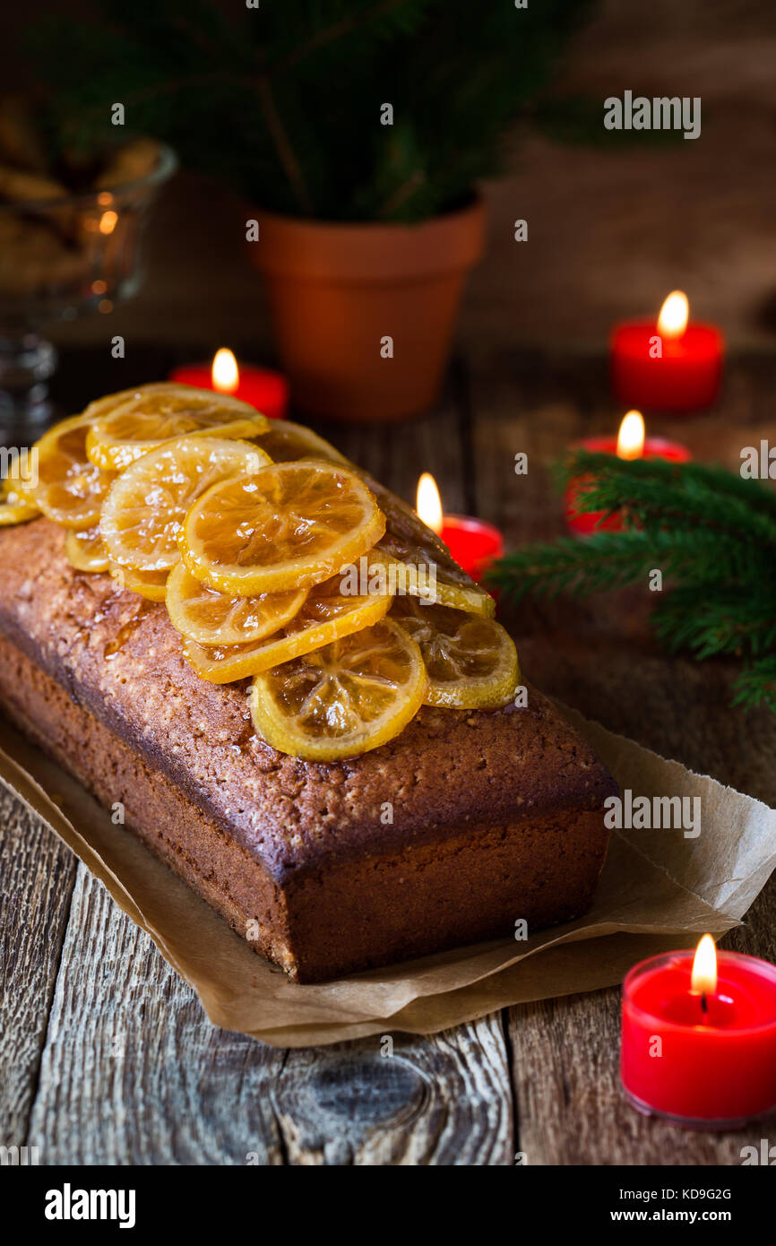 Homemade christmas lemon cake topped with  candied fruits on rustic wooden table - Stock Image