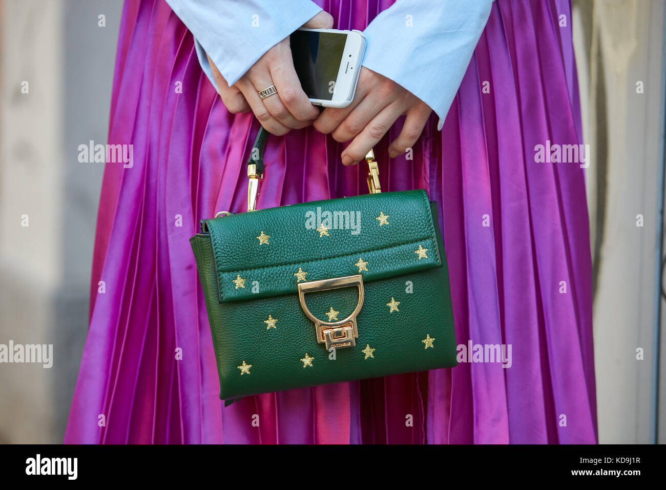 MILAN - SEPTEMBER 21  Woman with green Coccinelle leather bag with golden  stars and fuchsia metallic skirt before Fendi fashion show c38e4fcb74e61