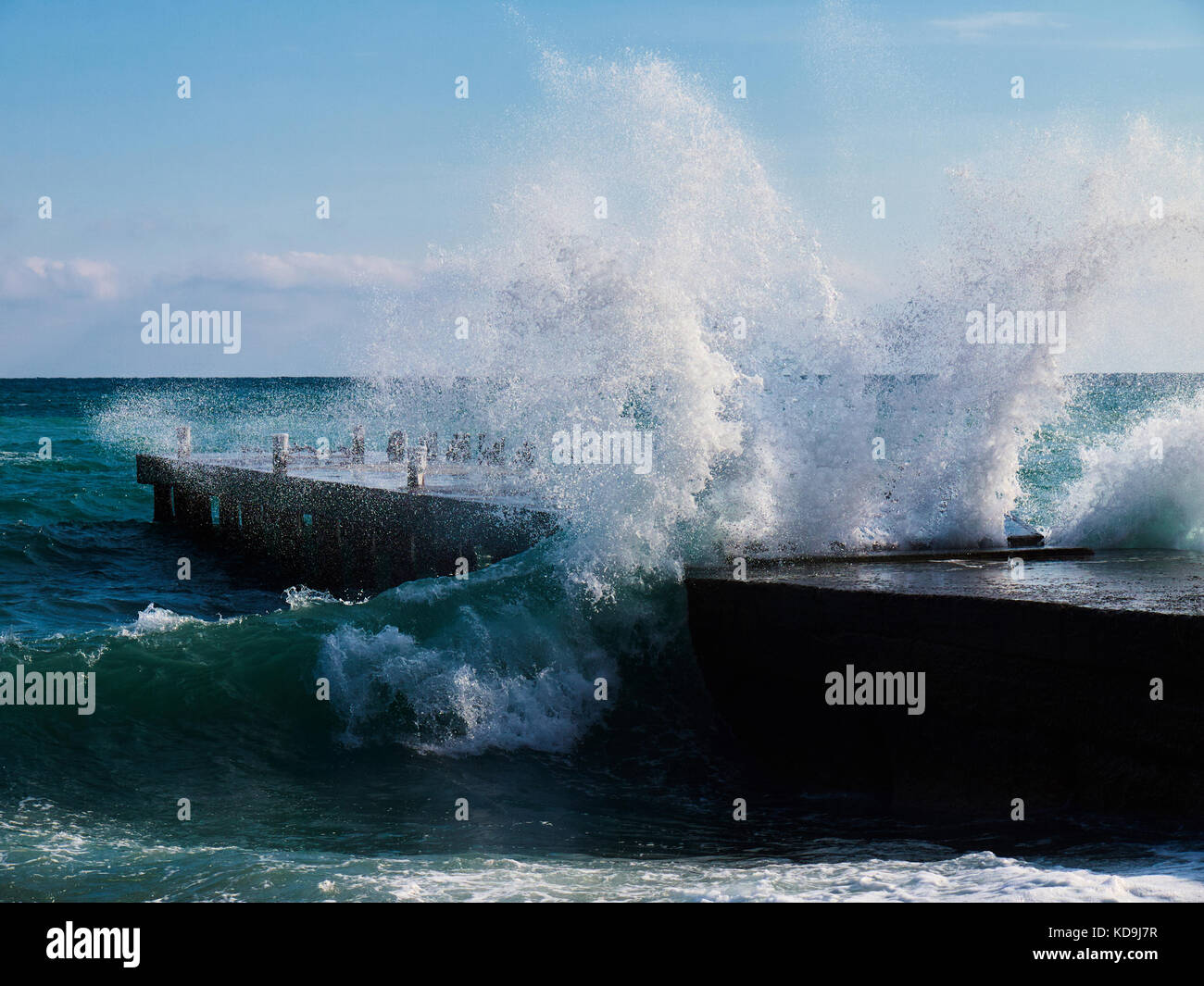 Big teal wave splashing out centre of empty stone pier with bollards on sunny winter day - Stock Image