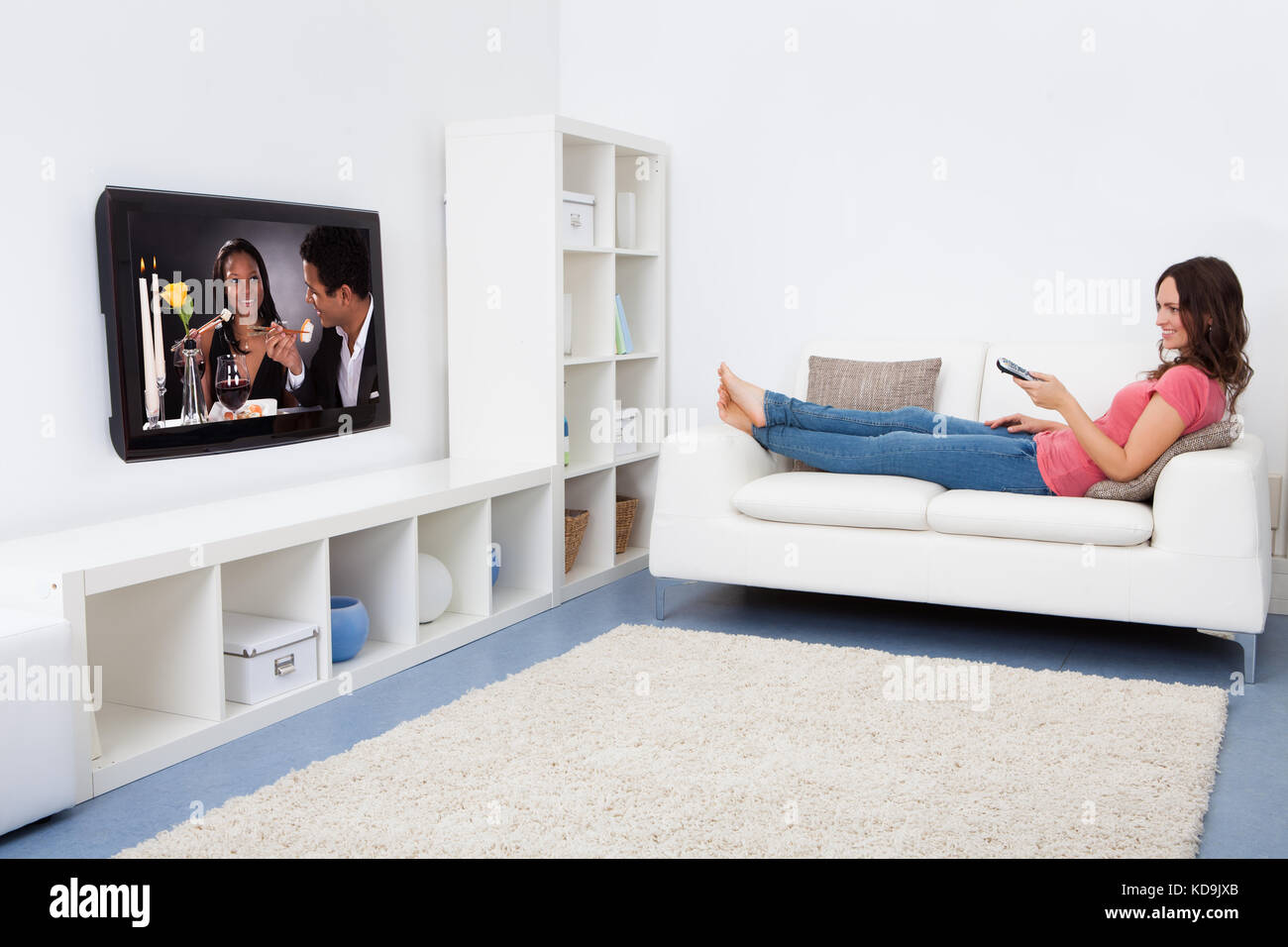 Portrait Of Smiling Woman Sitting On Couch Watching Television - Stock Image