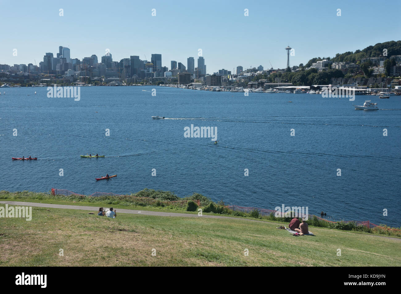 Tourists lounge on hill, aka The Mound -  at Gas Works Park overlooking scenic Lake Union, kayakers, Seattle skyline - Stock Image