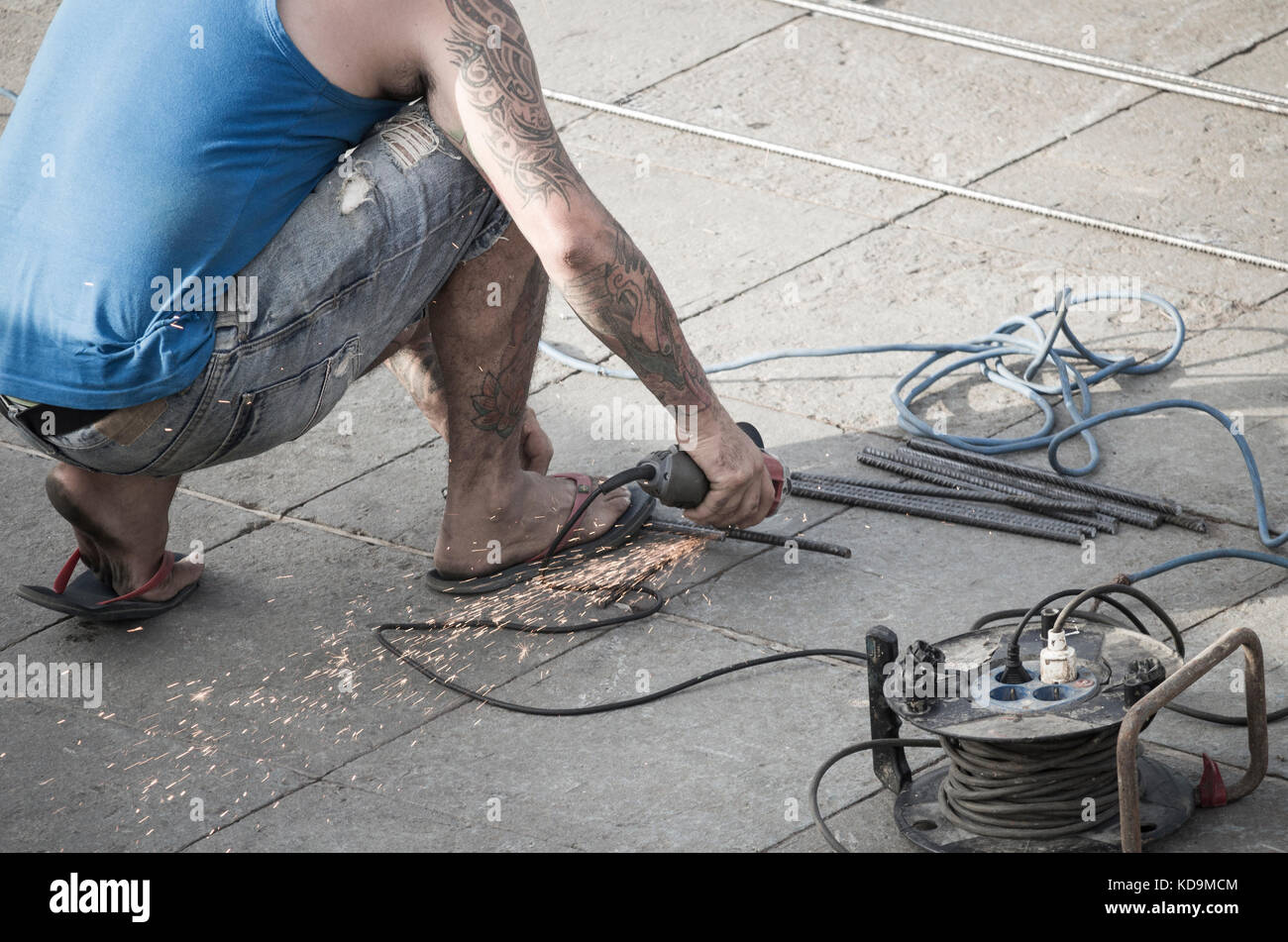 7c3448622 Man in Spain welding and grinding outdoors wearing flip flops Stock ...