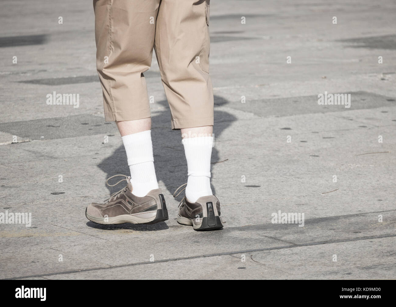 Rear view of tourist in Spain wearing three quarter length trousers and white socks. - Stock Image