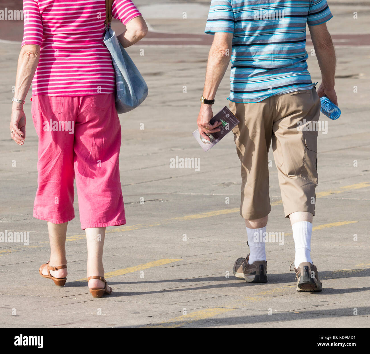 Rear view of mature couple wearing three quarter length trousers (man also wearing white socks) in Spain - Stock Image