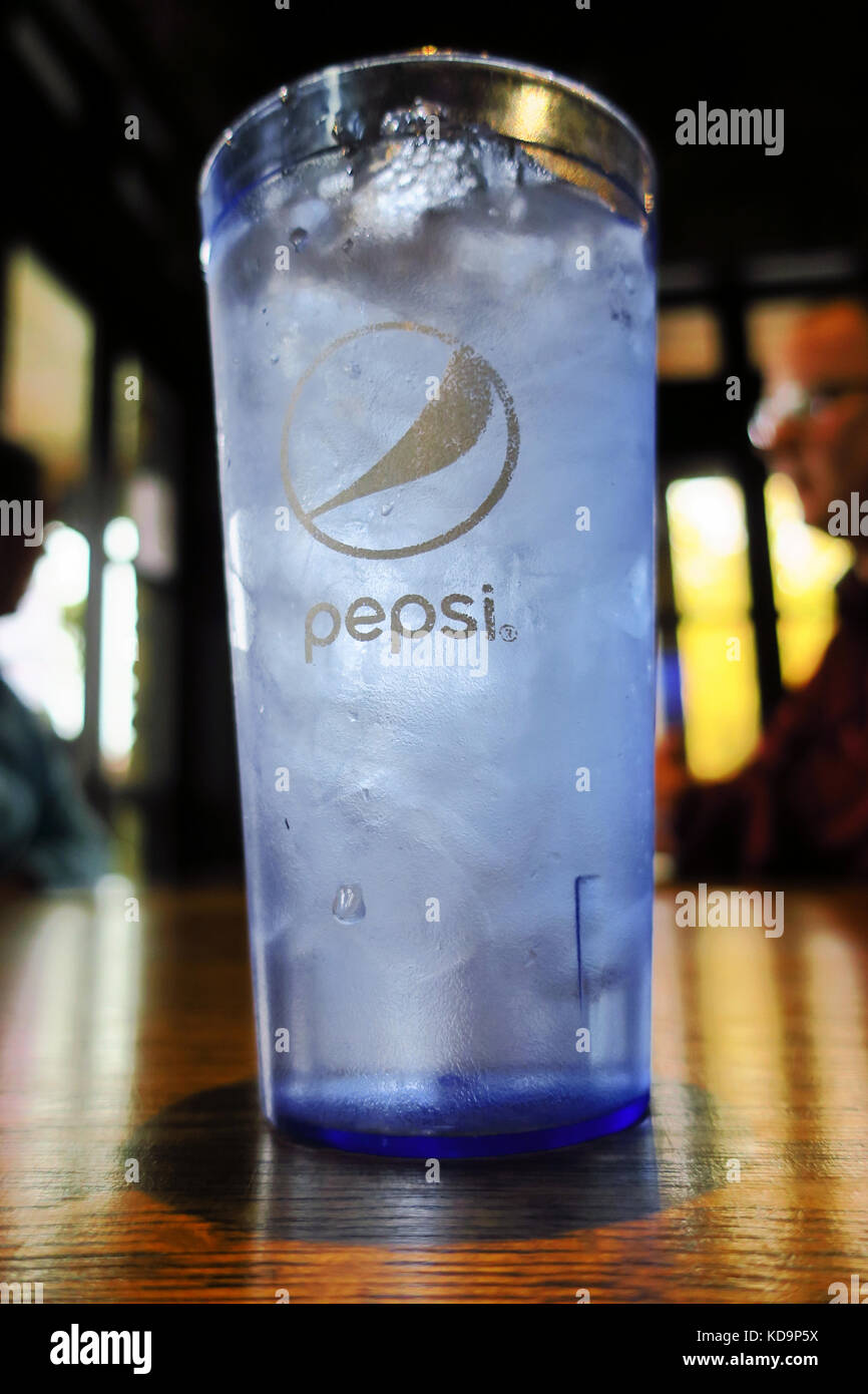 A pepsi glass with ice cold water on a table in a bar. - Stock Image
