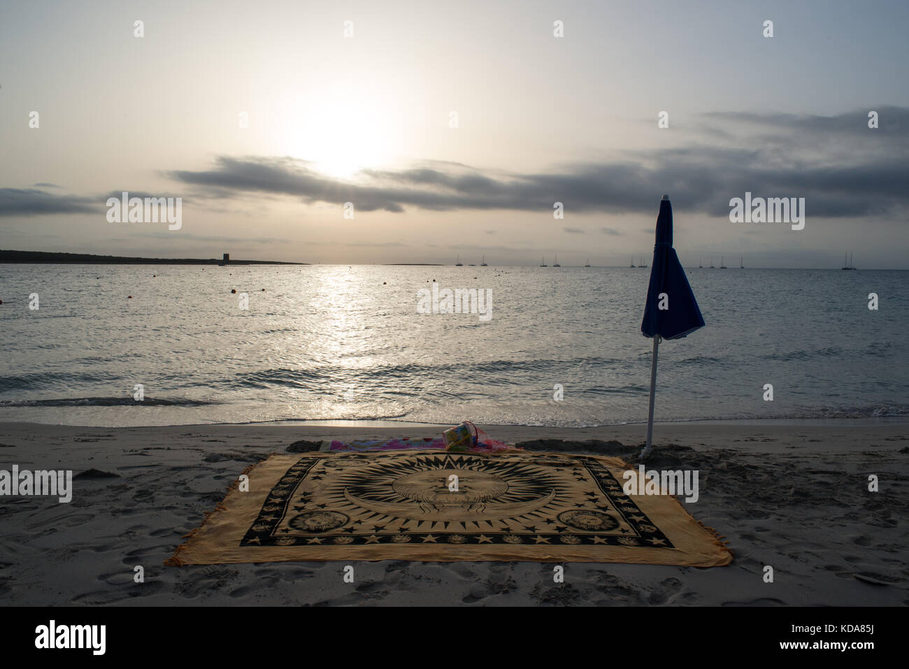 A scenic view of La Pelosa beach at sunrise in summer. A beach towel and umbrella in the sand with sea in background. - Stock Image