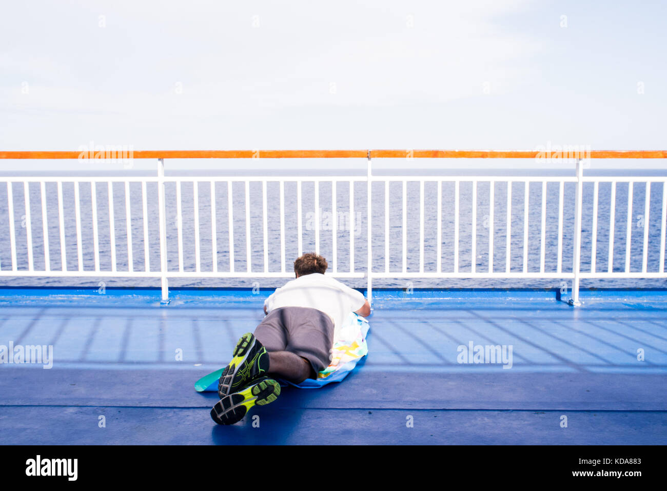 A man lying on the deck of a ship looks at the horizon while sailing on the Mediterranean Sea - Stock Image