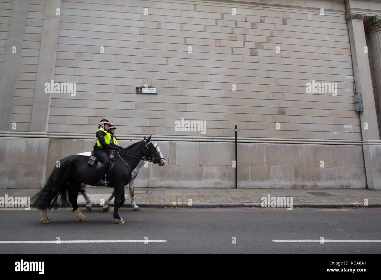 Police officers on horseback go past the Bank of England in Lothbury, city of London - Stock Image