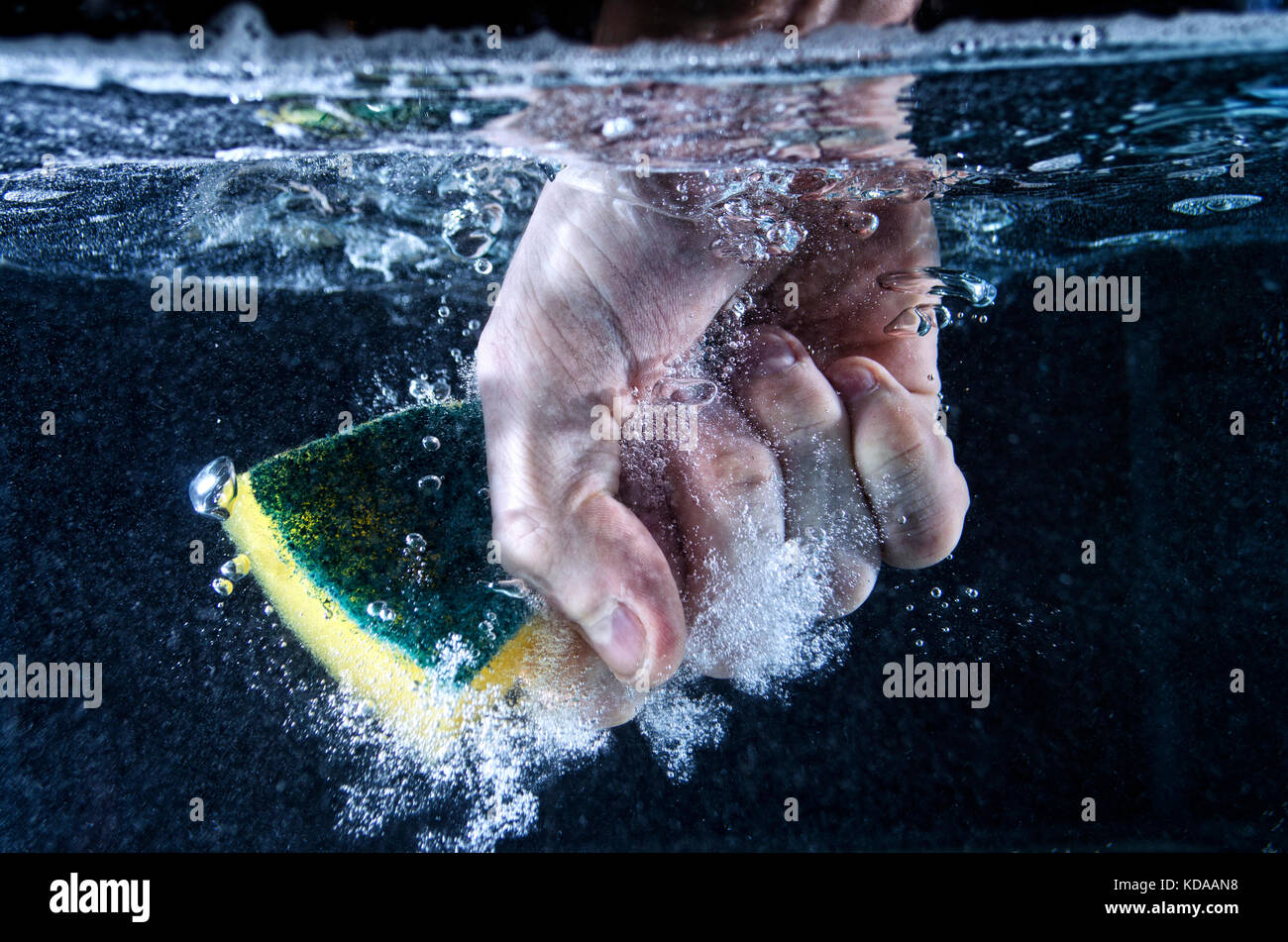 Hand Grabbing Sponge Under Water - Stock Image