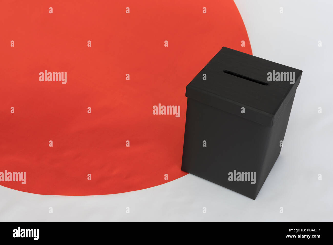 Japanese 'Circle of the Sun' / 'Rising Sun' flag with black ballot box - as metaphor for Japanese General Election. Stock Photo