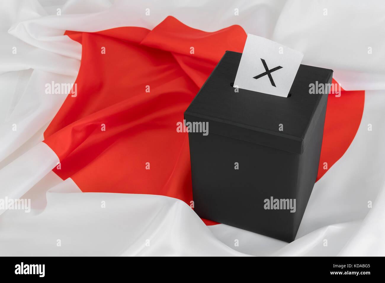 Japanese 'Circle of the Sun' / 'Rising Sun' flag with black ballot box - as metaphor for Japanese - Stock Image