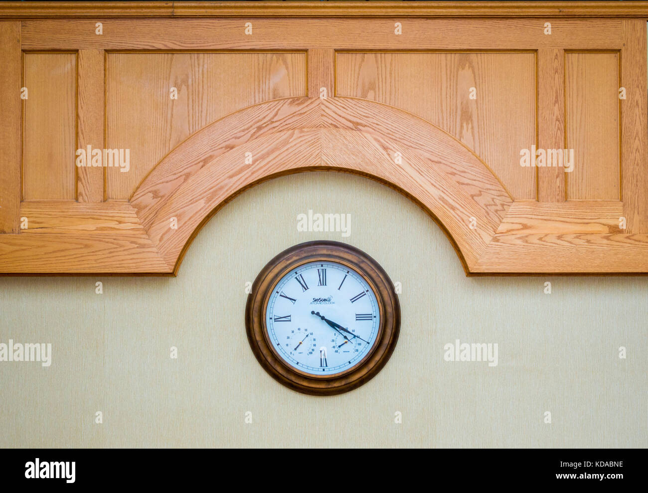 classic wall clock with Roman numerals beneath a carved wood panel - Stock Image