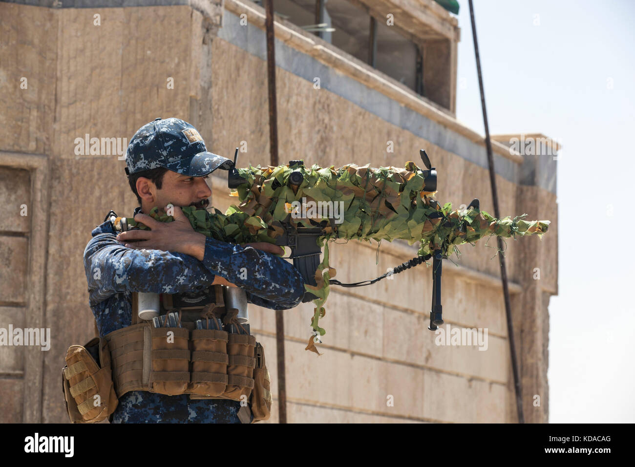 An Iraqi Federal Police sniper looks through the scope of his rifle on the roof of a patrol base June 29, 2017 in - Stock Image