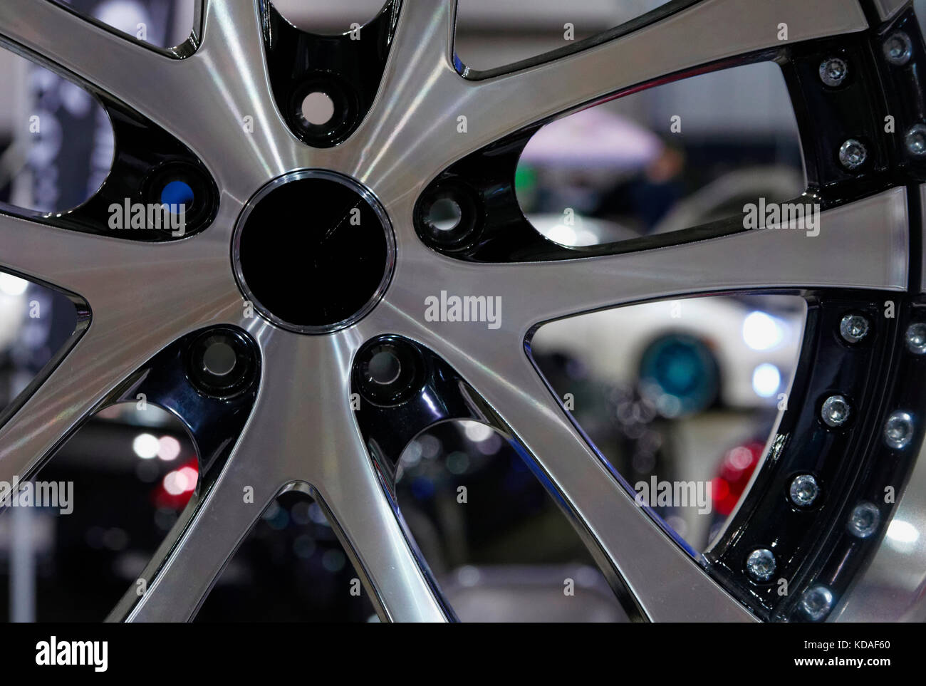 Custom metal wheels with black trim on display at a car show. - Stock Image