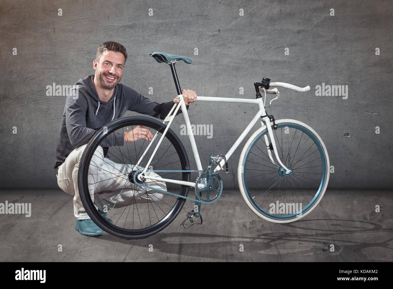 Happy cyclist next to custom made bicycle - Stock Image