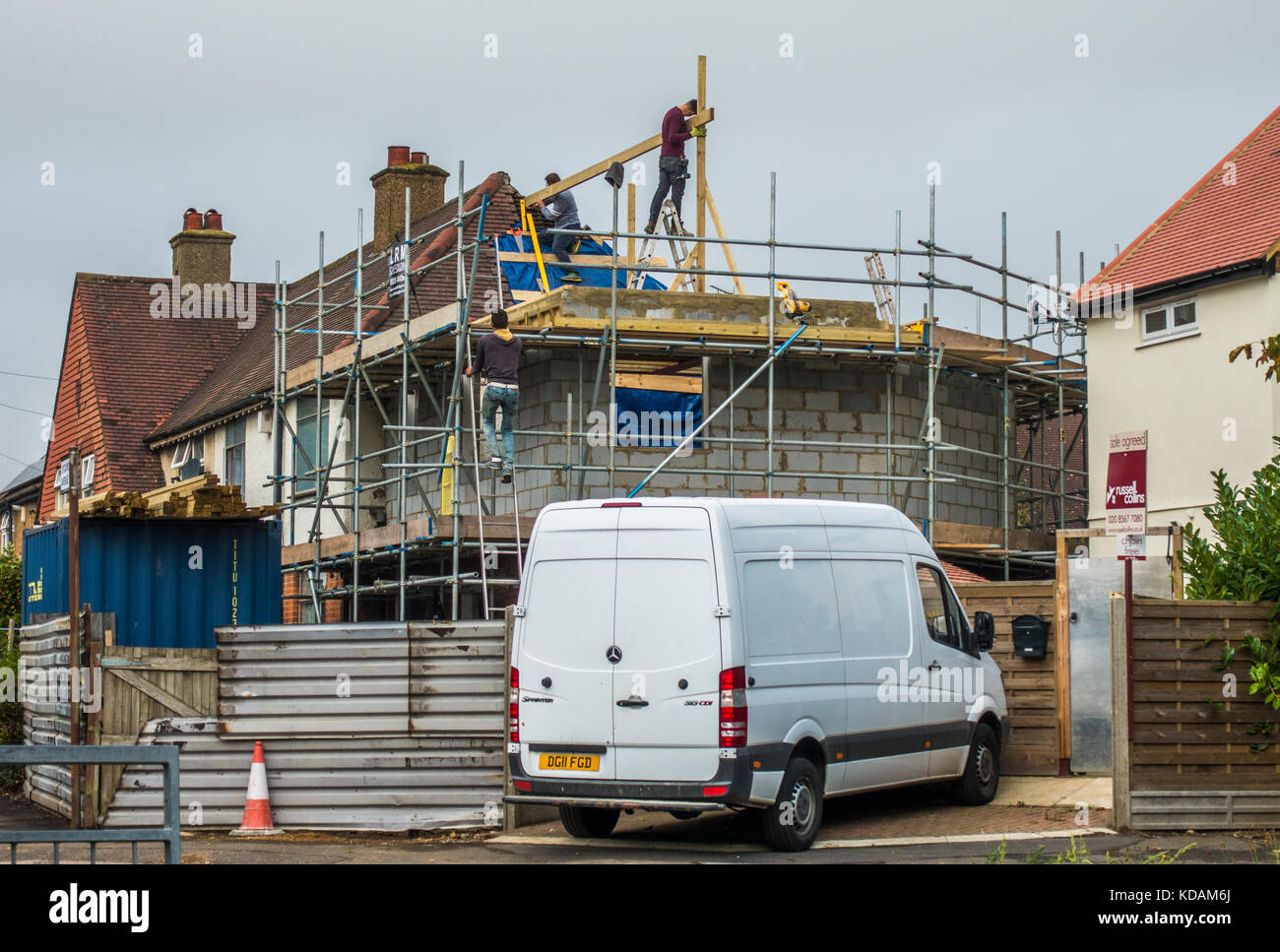 Builders, surrounded by scaffolding, working on the upper floor of a two storey corner house extension, in South - Stock Image
