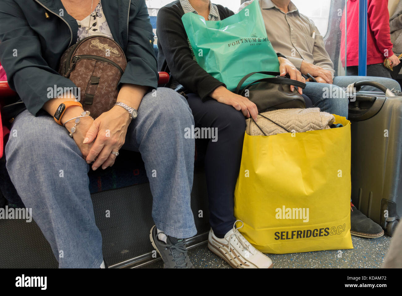 London Underground tube train - woman holding shopping bags from upmarket retailers Selfridges and Fortnum & - Stock Image