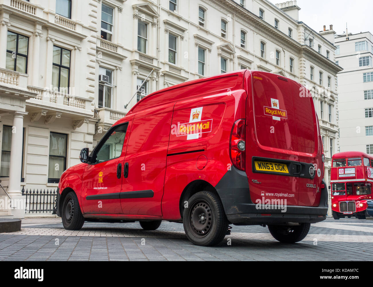 Royal Mail van parked in a street, outside period buildings, in South Kensington, with a traditional red bus approaching. - Stock Image