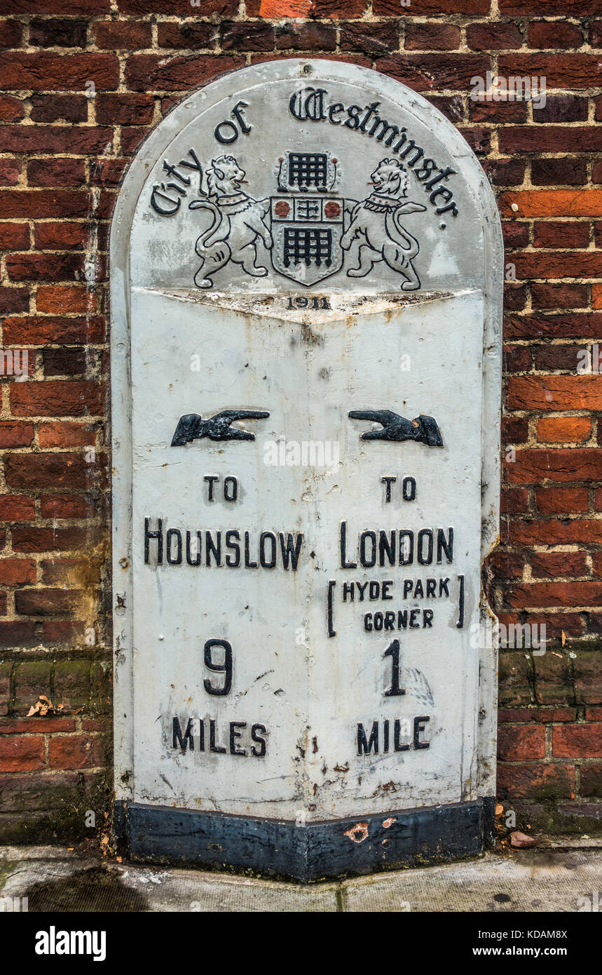 Old City of Westminster milestone, in need of repainting, showing distance to Hyde Park Corner and Hounslow, in - Stock Image